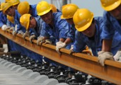 Workers lay a railway line as China infrastructure grows